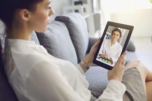 woman using tablet computer to talk to her doctor - telehealth